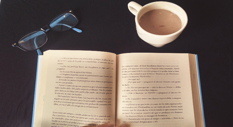 Libro-fisico-junto-a-una-taza-de-cafe-y-gafas
